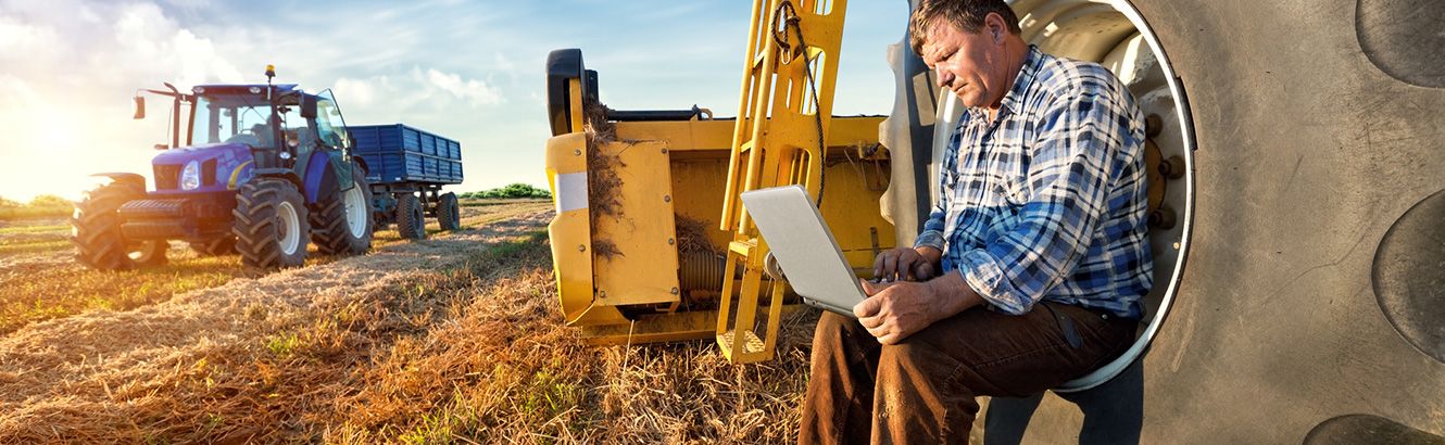 Farmer working on a laptop computer around farm equipment